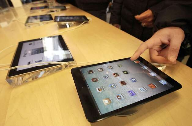 Shoppers at Apple's flagship store in New York, look at iPad and iPad Minis, Friday, Nov. 23, 2012.  Black Friday, the day when retailers traditionally turn a profit for the year, got a jump start this year as many stores opened just as families were finishing up Thanksgiving dinner. (AP Photo/Richard Drew) Photo: Richard Drew, Associated Press