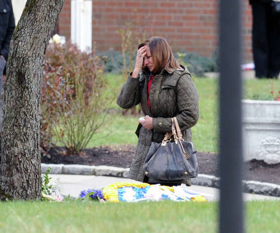 A woman stops at a shrine to pray at the conclusion of the Funeral Mass for Sandy Hook Elementary School student Olivia Rose Engel at St. Rose of Lima Roman Catholic Church in Newtown, Friday afternoon, Dec. 21, 2012. Photo: Bob Luckey / Greenwich Time