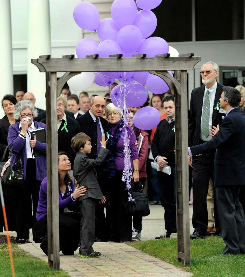 Jake Hockley, with his mother Nicole, behind him, releases 26 balloons in memory of the 26 victims of the Sandy Hook Elementary School shooter. The balloons were released at the conclusion of a funeral service for Jake's brother, Dylan Hockley, one of the victims, at Walnut Hill Community Church in Bethel, Conn. Friday, Dec. 21, 2012. Photo: Carol Kaliff / The News-Times