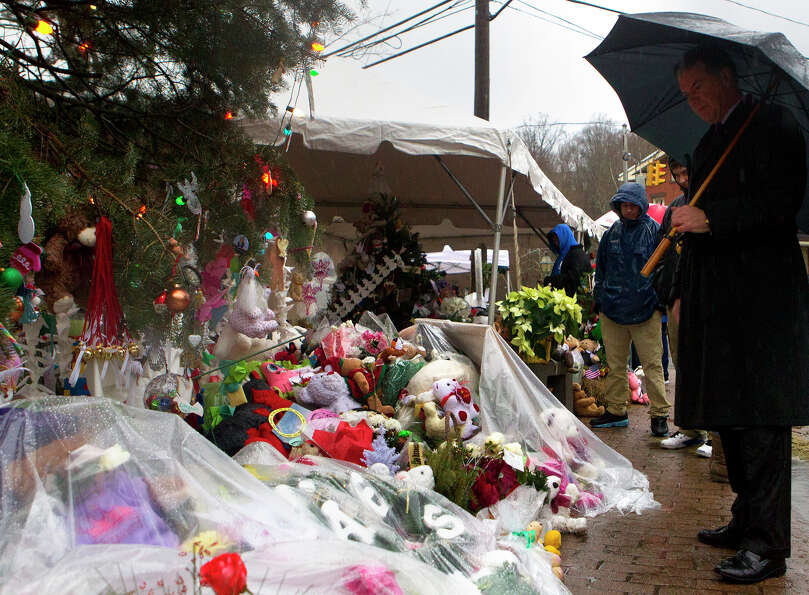 Portions of a memorial site are covered to protect them from the rain Friday, December 21, 2012 in N