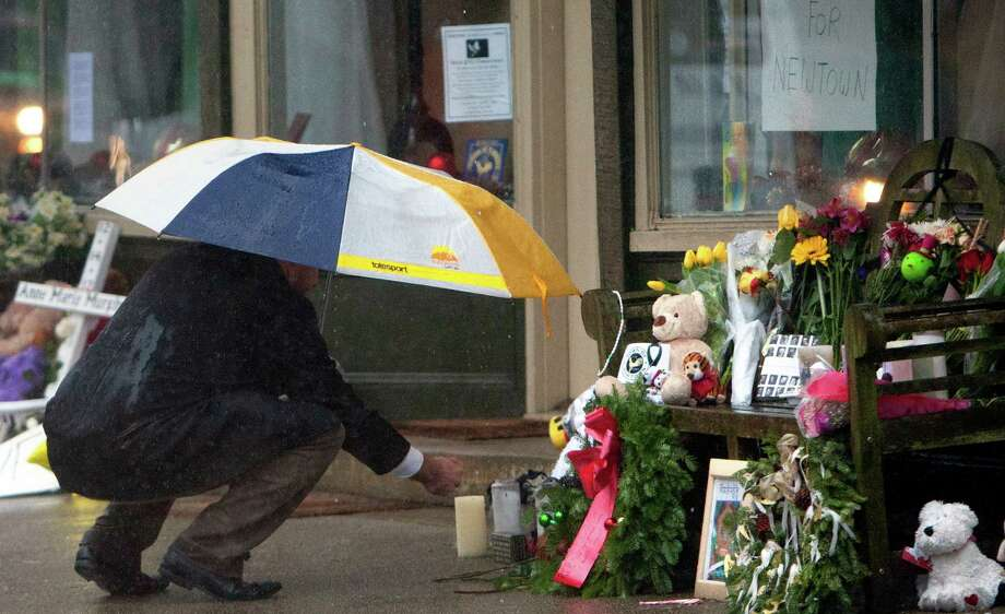Portions of a memorial site are covered to protect them from the rain Friday, December 21, 2012 in Newtown, Conn., honoring the individuals who were killed during a shooting at Sandy Hook Elementary School last Friday. The school was evacuated after Adam Lanza opened fire killing 26 individuals, 20 whom were children. Photo: Cody Duty, Cody Duty/Hearst Newspapers / The News-Times