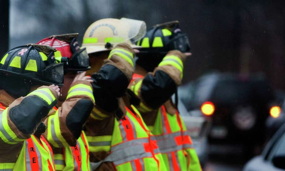 Firefighters salute the precession for the funeral of Rachel Marie D'Avino as it enters the Church of the Nativity in Bethlehem, Connecticut, Friday, December 21, 2012. D'Avino was killed during a shooting at Sandy Hook Elementary School last Friday. The school was evacuated after Adam Lanza opened fire killing 26 individuals, 20 whom were children. Photo: Cody Duty, Cody Duty/Hearst Newspapers / The News-Times
