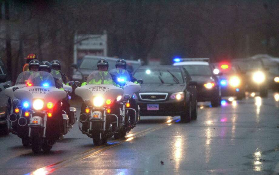 The precession for Rachel Marie D'Avino drives to the Church of the Nativity in Bethlehem, Connecticut, for her funeral Friday, December 21, 2012. D'Avino was killed during a shooting at Sandy Hook Elementary School last Friday. The school was evacuated after Adam Lanza opened fire killing 26 individuals, 20 whom were children. Photo: Cody Duty, Cody Duty/Hearst Newspapers / The News-Times