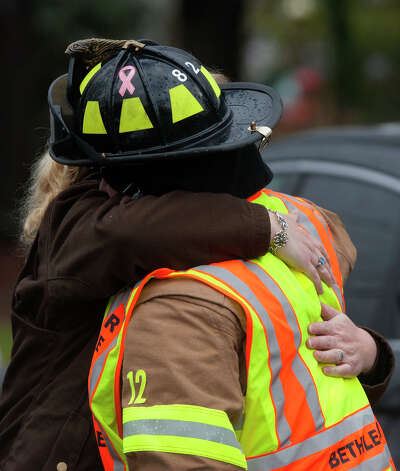 A woman hugs a firefighter outside of the funeral for Rachel Marie D'Avino at the Church of the Nativity in Bethlehem, Connecticut, Friday, December 21, 2012. D'Avino was killed during a shooting at Sandy Hook Elementary School last Friday. The school was evacuated after Adam Lanza opened fire killing 26 individuals, 20 whom were children. Photo: Cody Duty, Cody Duty/Hearst Newspapers / The News-Times