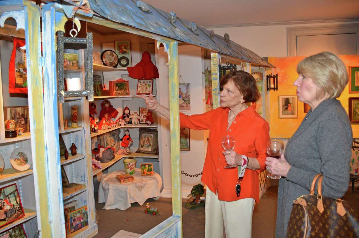 Janet Lindstrom, Executive Director of the New Canaan Historical Society, points out to Inger Stringfellow some of the thousands of interesting items in the Little Red Riding Hood exhibit during the opening. Nov. 30, 2012.