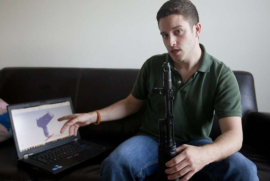 Cody Wilson of the group Defense Distributed shows an image of a prototype plastic gun on a computer screen while holding anther. Photo: Alberto Martinez, Associated Press