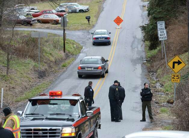 Local law enforcement block off road along Rt. 22 near the Canoe Creek State Park, Pa. while investigating a shooting on Friday, Dec. 21, 2012.   The suspect fired at troopers responding to Friday morning's shootings in Frankstown Township, about 70 miles west of Harrisburg. The fleeing gunman then crashed head-on into a trooper's car and got out of his truck and shot again at police, who returned fire and killed him. Blair County District Rich Consiglio says the gunman killed two men and one woman. (AP Photo/Altoona Mirror,  J.D. Cavrich) Photo:  J.D. Cavrich, MBR / Altoona Mirror