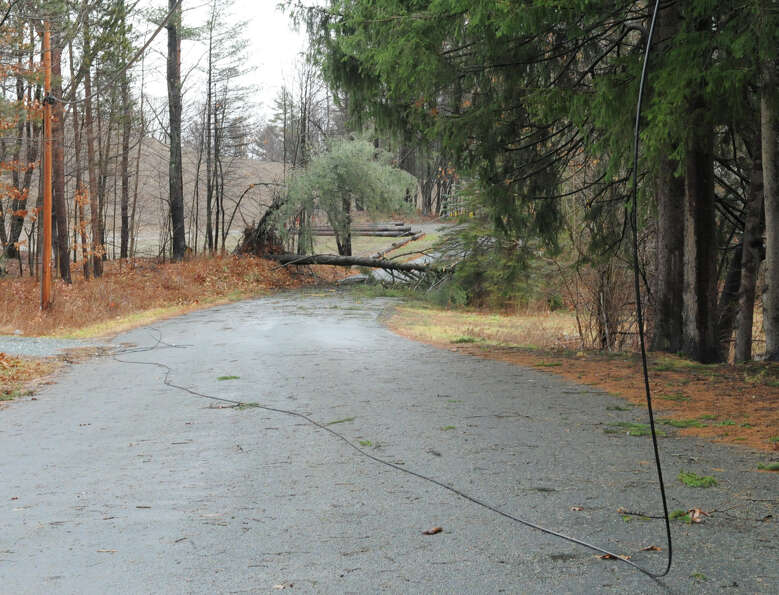 Part of a road is closed due to a down wire and tree from high winds and rain on Friday Dec. 21, 201