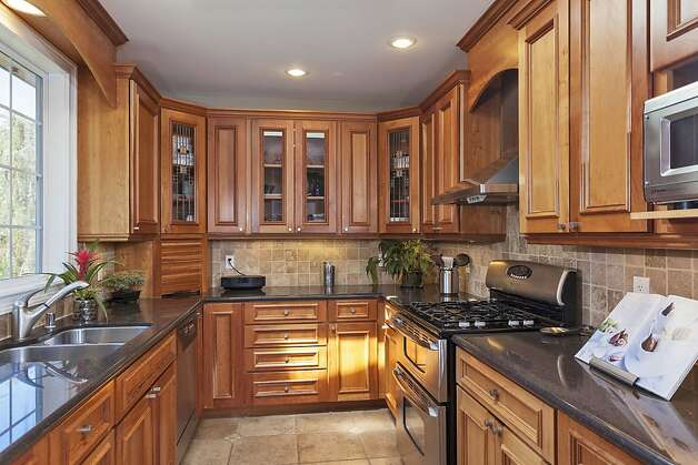 Tile backsplashes and flooring complement the hardwood cabinets in the brand-new kitchen. Photo: Scott Hargis/SF