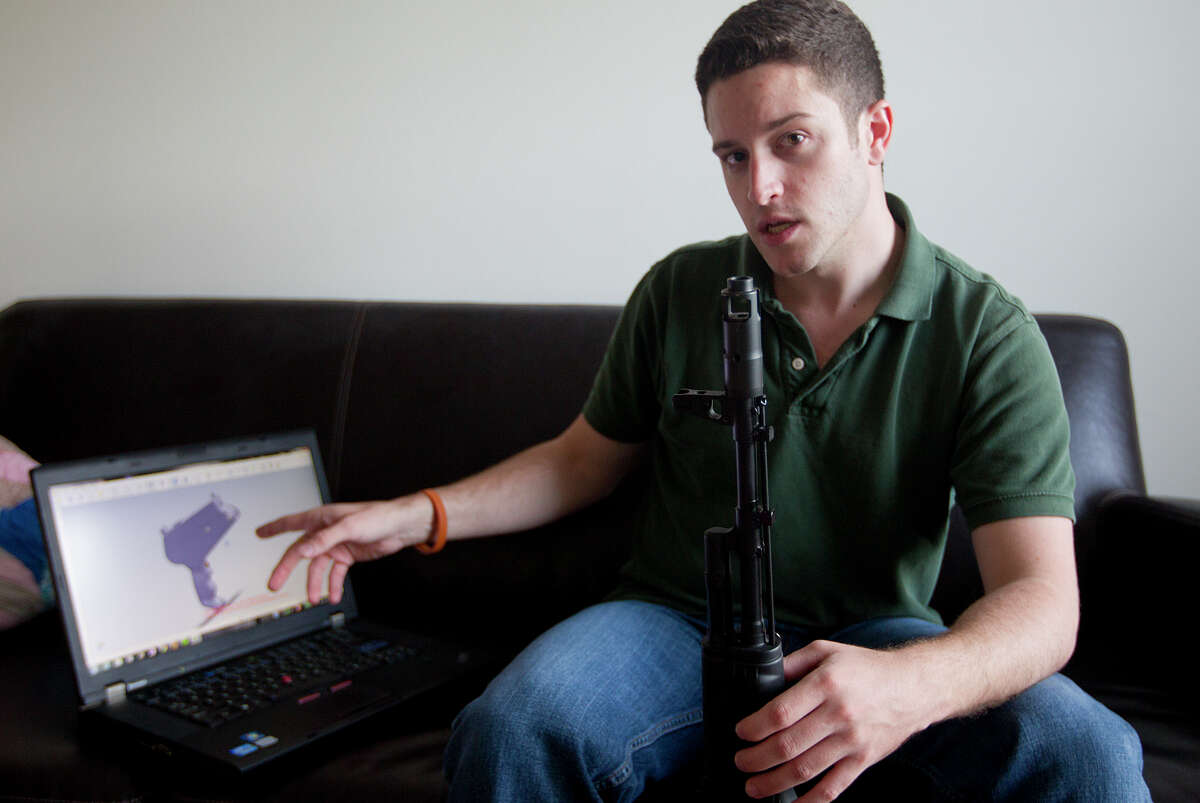 """In this Oct. 3, 2012 photo, """"Wiki Weapons"""" project leader Cody Wilson points to his laptop screen displaying an image of a prototype plastic gun on the screen, while holding in his other a weapon he calls """"Invivdual Mandate,"""" in Austin, Texas. At least one group, called Defense Distributed, is claiming to have created downloadable weapon parts that can be built using the increasingly popular new-generation of printer that utilizes plastics and other materials to create 3-D objects with moving parts. Wilson says the group last month test fired a semiautomatic AR-15 rifle - one of the weapon types used in the Connecticut elementary school massacre - which was built with some key parts created on a 3-D printer. The gun was fired six times before it broke. (AP Photo/Statesman.com, )"""