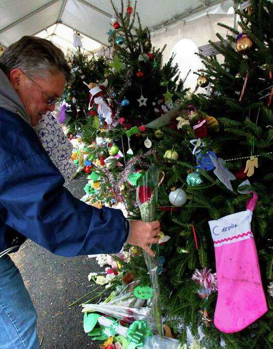 """Long Island Navy Veteran Michael Kennedy places a rose on a Christmas tree at a memorial in front of Sandy Hook Elementary School, Friday, December 21, 2012 in Newtown, Connecticut. Kennedy placed a rose on each of the 26 trees for each person who died after gunman Adam Lanza opened fire killing 26 individuals, 20 whom were children, last Friday. """"I have to do this before I'm dedicated to ridding our society of guns,"""" Kennedy said. """"I'm going to do whatever I can to ban assault weapons and multiple clips. Our society is not defined by the NRA. It should never be defined by any extremist group. I consider them extremist."""" Photo: Cody Duty, Cody Duty/Hearst Newspapers / The News-Times"""