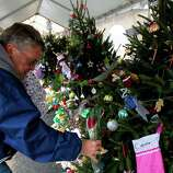 "Long Island Navy Veteran Michael Kennedy places a rose on a Christmas tree at a memorial in front of Sandy Hook Elementary School, Friday, December 21, 2012 in Newtown, Connecticut. Kennedy placed a rose on each of the 26 trees for each person who died after gunman Adam Lanza opened fire killing 26 individuals, 20 whom were children, last Friday. ""I have to do this before I'm dedicated to ridding our society of guns,"" Kennedy said. ""I'm going to do whatever I can to ban assault weapons and multiple clips. Our society is not defined by the NRA. It should never be defined by any extremist group. I consider them extremist."""