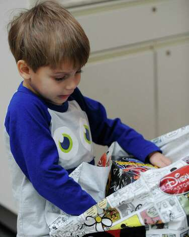 Owen Immenschuh, 3, looks through purchases made by his mother, Charlotte, at North Star Mall on Friday, Dec. 21, 2012. Photo: Billy Calzada, San Antonio Express-News / SAN ANTONIO EXPRESS-NEWS