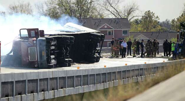 Houston Firefighters try to put out a fire on an overturned 18-wheeler on the ramp from I-10 to 59 Northbound after an accident, Friday, Dec. 21, 2012, in Houston. Photo: Karen Warren, Houston Chronicle / © 2012 Houston Chronicle