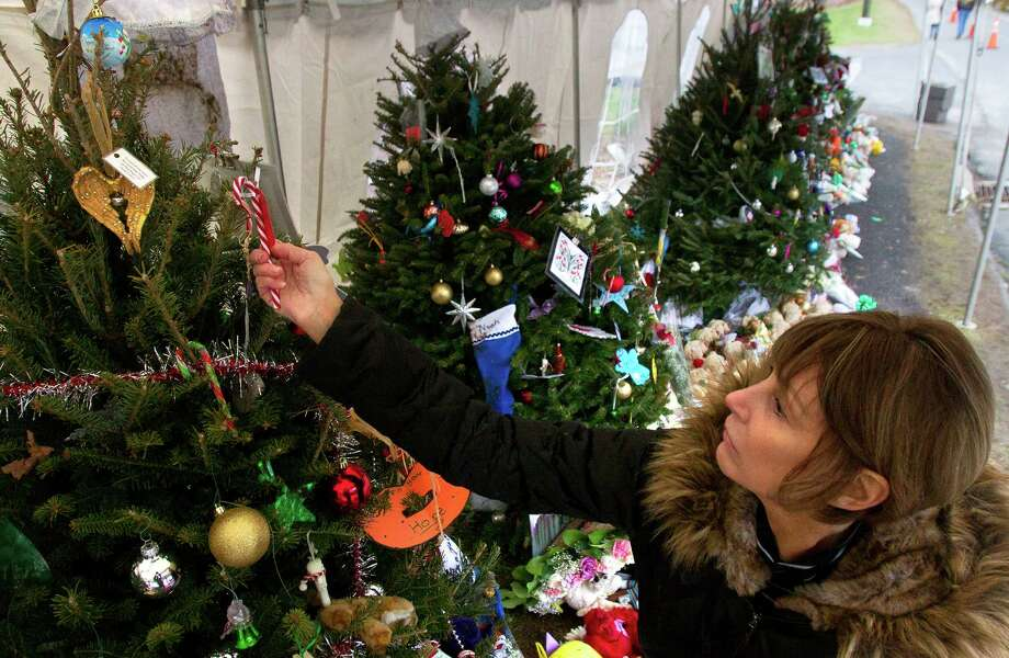 """T.D. Grimes prepares a candy cane before hanging it on a Christmas tree at a memorial in front of Sandy Hook Elementary School, Friday, December 21, 2012 in Newtown, Connecticut. Grimes placed a cane on each tree remembering a student and an apple on each tree remembering each teacher who died after gunman Adam Lanza opened fire in the school last Friday. """"My sole was rattling around, restless that I needed to do something,"""" she said. """"I couldn't take doing nothing."""" Photo: Cody Duty, Cody Duty/Hearst Newspapers / The News-Times"""