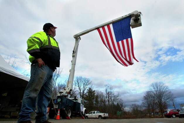 "Kevin Yacko looks at an American flag hung by he and his son, Thomas, as it flies at the ""Exit 10 Chapel"" in honor of the 26 people killed at Sandy Hook Elementary School. The two set up a makeshift memorial in an otherwise unremarkable vacant lot after the shooting took place. âÄúWeâÄôve flown this flag in happier times, and weâÄôre very close to what happened in Sandy Hook,âÄù Kevin said. âÄúSo we set up the truck and the flag and within one hour, someone brought a small blue tent. Then candles came, teddy bears, flowers, a piece of carpet, a board to sign.âÄù Photo: Cody Duty, Cody Duty/Hearst Newspapers / The News-Times"