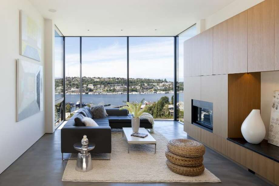 Living room of 814 E. Blaine St., has two bedrooms, 1.75 bathrooms, concrete floors, a floating staircase, walls of windows and a view deck looking over Lake Union. It's listed for $1.5 million. Photo: Courtesy Sandra Pappas/Windermere Real Estate