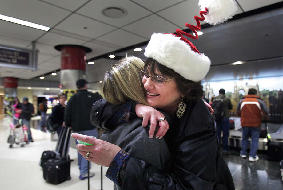 Diane Ellegood, right, is greeted by her sister Dorothy Oakes at the San Antonio International Airport, with a hug and a lime green Margarita Jello Shot, which surprised Ellegaood and her husband Joe Ellegood, after they arrived from St. Louis for the holidays. Dec. 21, 2012 is one of the busiest air travel days of the year at San Antonio International Airport. Photo: Bob Owen, San Antonio Express-News / ©SAN ANTONIO EXPRESS-NEWS