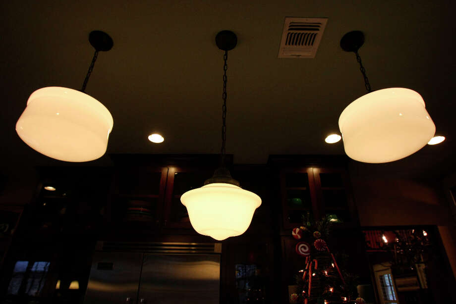 Milk glass globe lights in the kitchen of Leo and Karen Scherrer's  home in New Braunfels. Photo: Helen L. Montoya, San Antonio Express-News / ©SAN ANTONIO EXPRESS-NEWS