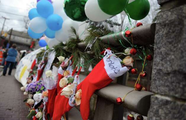 Stockings for victims of the Sandy Hook Elementary School shooting hang along a bridge near a memorial in Newtown, Conn. Friday, Dec. 21, 2012 Photo: Autumn Driscoll / Connecticut Post