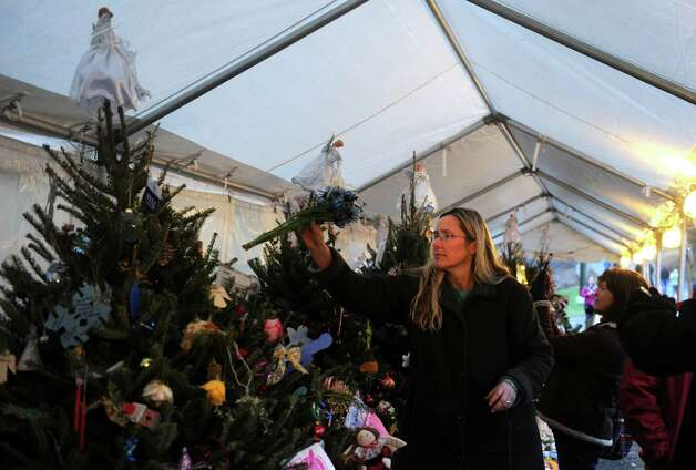 A woman decorates Christmas trees set up in Newtown, Conn. Friday, Dec. 21, 2012 for the victims of the Sandy Hook Elementary School shooting. Photo: Autumn Driscoll / Connecticut Post