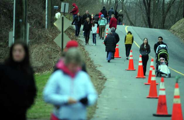 People walk up the road leading to Sandy Hook Elementary School in Newtown, Conn. Friday, Dec. 21, 2012 to visit a memorial for the victims of last Friday's school shooting. Photo: Autumn Driscoll / Connecticut Post