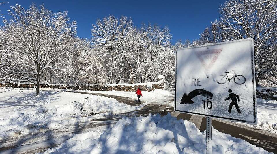 A pedestrian makes her way along a cleared path in Madison, Wis., where a foot of snow fell.