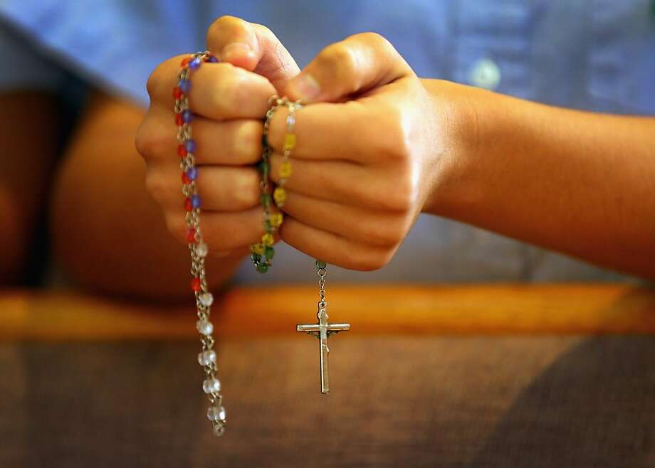 A child holds rosary beads as she prays during a service at St. Rose of Lima School, for the victims of  the school shooting one week ago in Newtown, Connecticut on December 21, 2012 in Miami, Florida. Across the country people marked the one week point since the shooting at Sandy Hook Elementary School in Newtown, Connecticut that killed 26 people. Photo: Joe Raedle, Getty Images