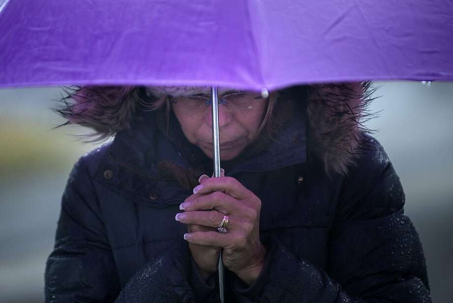 A woman bows her head during a moment of silence in Sandy Hook village on December 21, 2012 in Newtown, Connecticut. People around the United States joined in a moment of silence at 9:30 am to mark the one week anniversary of the Sandy Hook Elementary School shootings, while bells also rang 26 times to honor the victims of alleged gunman Adam Lanza, not including his mother Nancy Lanza who was killed at their family home. Photo: Brendan Smialowski, AFP/Getty Images