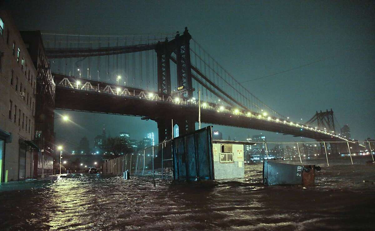 In this Oct. 29, 2012 file photo, streets in the Brooklyn borough of New York are flooded under the Manhattan Bridge as a surge of seawater is pushed into New York City by Superstorm Sandy. The weather in 2012 was deadly, costly and record-breaking everywhere _ but especially in the United States. (AP Photo/Bebeto Matthews, File)