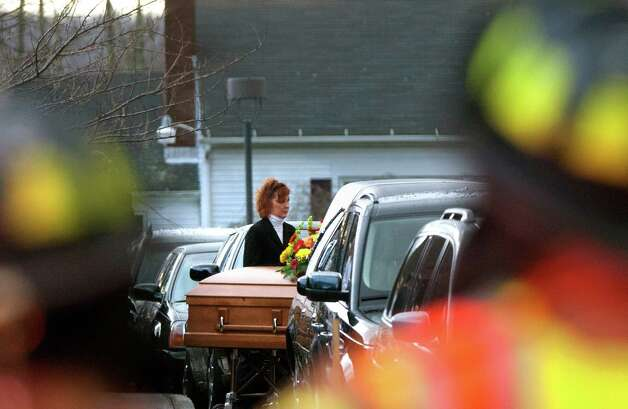 A woman watches as the casket of Rachel Marie D'Avino is loaded into the hearse at the Church of the Nativity in Bethlehem, Connecticut, Friday, December 21, 2012. D'Avino was killed during a shooting at Sandy Hook Elementary School last Friday. The school was evacuated after Adam Lanza opened fire killing 26 individuals, 20 whom were children. Photo: Cody Duty, Cody Duty/Hearst Newspapers / The News-Times