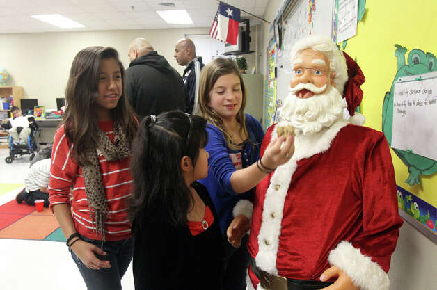 Mandy Dallenbach,11, tries to feed a Santa Claus doll a cookie at the annual Christmas party for teacher Leticia Ledesma's special education students at Barkley-Ruiz Elementary school Friday December 21, 2012. On the left (wearing red shirt with white stripes) is Gianna Fuentes,11, and in the middle is Jessica Thomas,8. Dallenbach and Fuentes are volunteers that help put on the party and Thomas is a student in Ledesma's class. Ledesma buys gifts for the students with her own money and gathers donations on her own to give the students gifts. Photo: JOHN DAVENPORT, San Antonio Express-News / ©San Antonio Express-News/Photo Can Be Sold to the Public
