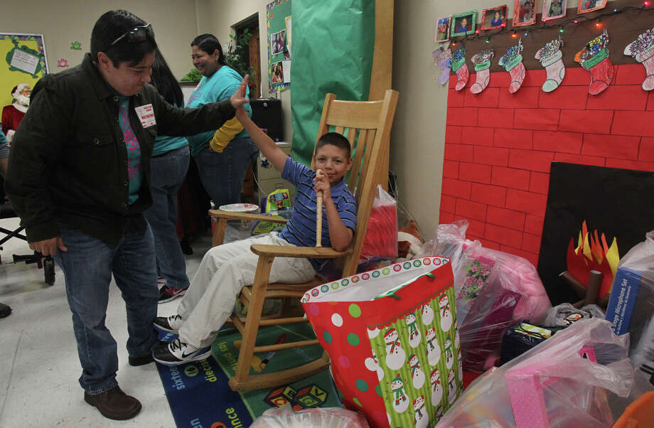Volunteer Alyssa Maldonado (left) gives student Gus Diaz (seated),9, a high five at the annual Christmas party for teacher Leticia Ledesma's special education students at Barkley-Ruiz Elementary school Friday December 21, 2012. Ledesma buys gifts for the students with her own money and gathers donations on her own to give the students gifts. Photo: JOHN DAVENPORT, San Antonio Express-News / ©San Antonio Express-News/Photo Can Be Sold to the Public