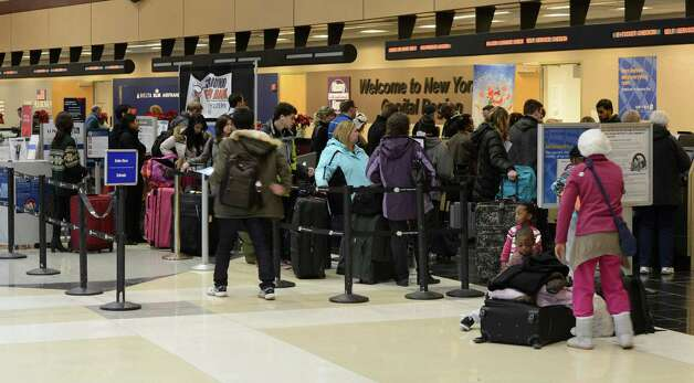 Travelers line up at the United Airlines counter at the Albany International Airport in Colonie, N.Y. to get rerouted due to a cancellation of the flight to Dulles in Washington D.C. this afternoon Dec. 21, 2012.      (Skip Dickstein/Times Union) Photo: Skip Dickstein / 00020558A