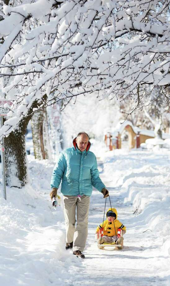 Frank Gloss pulls his grandson, Liam, 17 months old, along a sidewalk December 21, 2012 in Madison, Wisconsin, a day after Wisconsin was blanketed with a record snow storm. Photo: Andy Manis, Getty Images / 2012 Getty Images