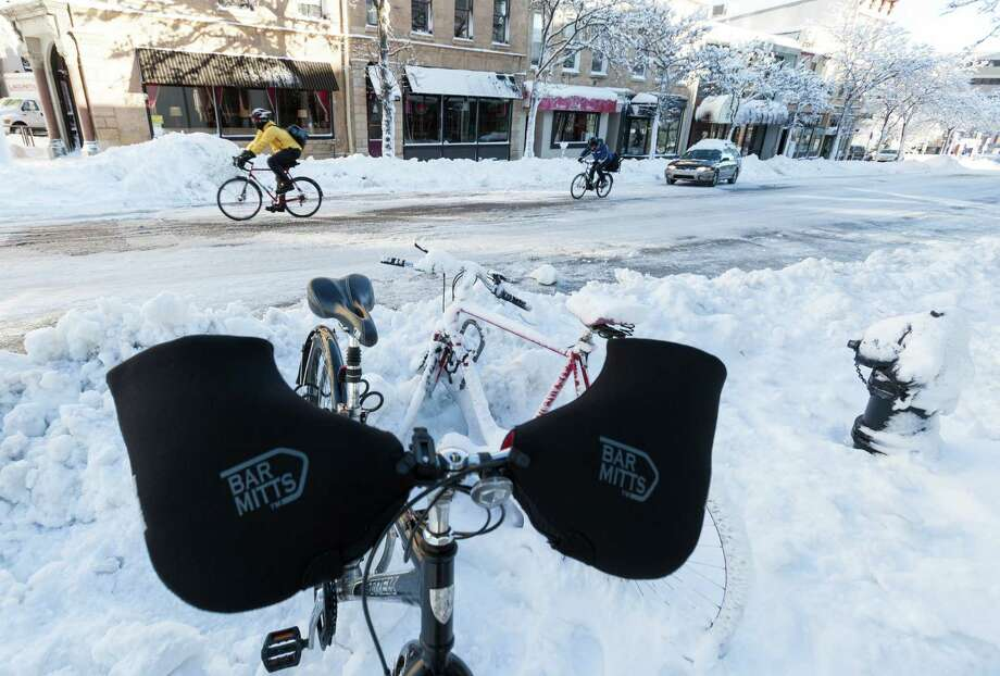 Cyclists ride up a street December 21, 2012 in downtown Madison, Wisconsin, a day after Wisconsin was blanketed with a snow storm. Photo: Andy Manis, Getty Images / 2012 Getty Images