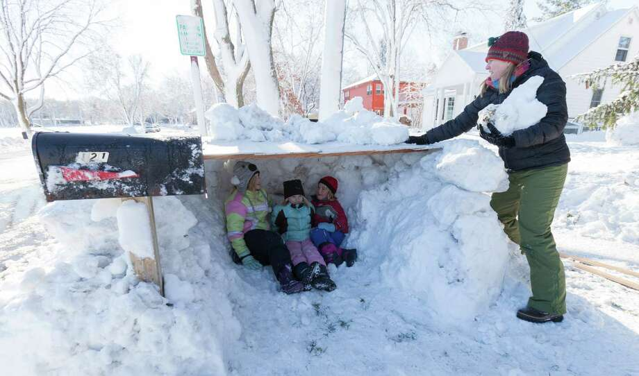 Elise Schmitt, left, 10, Julia Schmitt, 6, and their cousin Willa Treichel, right, 6, check out their newly made snow fort as Ellie Schmitt adds snow to the roof in Madison, Wis. Photo: Andy Manis, Stringer / 2012 Getty Images