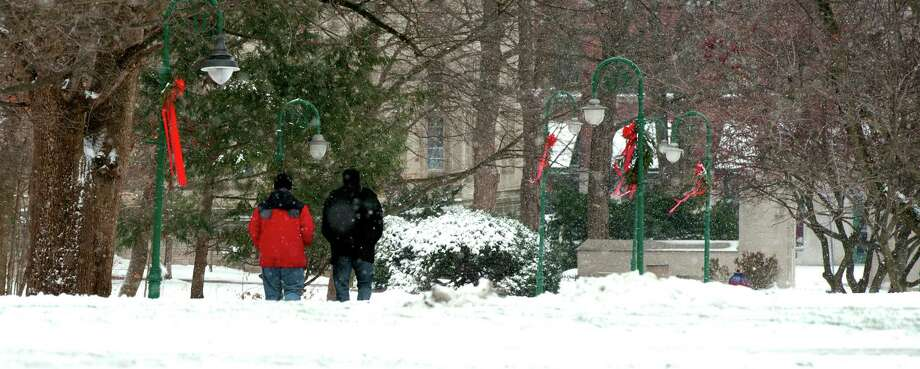 Two people walk through the snow on the Indiana University campus Friday, Dec. 21, 2012 in Bloomington, Ind. The area received about an inch of snow with howling winds through the night. Photo: David Snodgress, MBR / Bloomington Herald-Times