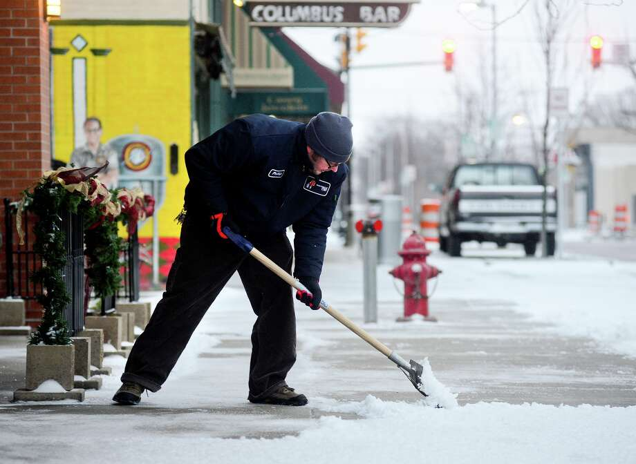 Department of Parks and Recreation employee Phillip Forney shovels snow and ice in downtown Columbus, Ind., Friday, Dec. 21, 2012. The most wintery weather in nearly a year blew into southern Indiana overnight closing or delaying many area schools, slowing traffic at times, and precipitating a few slides-offs. Photo: Joe Harpring, MBR / The Republic