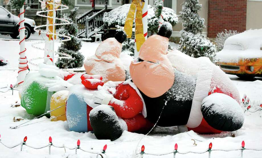 Mickey and Minnie Mouse inflatable Christmas decorations lie on the ground after the first snow of the season in Kansas City, Mo. Thursday, Dec. 20, 2012.  Photo: Fred Blocher, MBI / The Kansas City Star