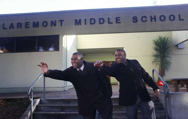 Ronald and Reginald Richardson, 36, who share the job as co-principals at Claremont Middle School, wave to parents at the start of another day. The identical twins, Oakland natives, come from a family of educators. Photo: Mike Kepka, The Chronicle / SF