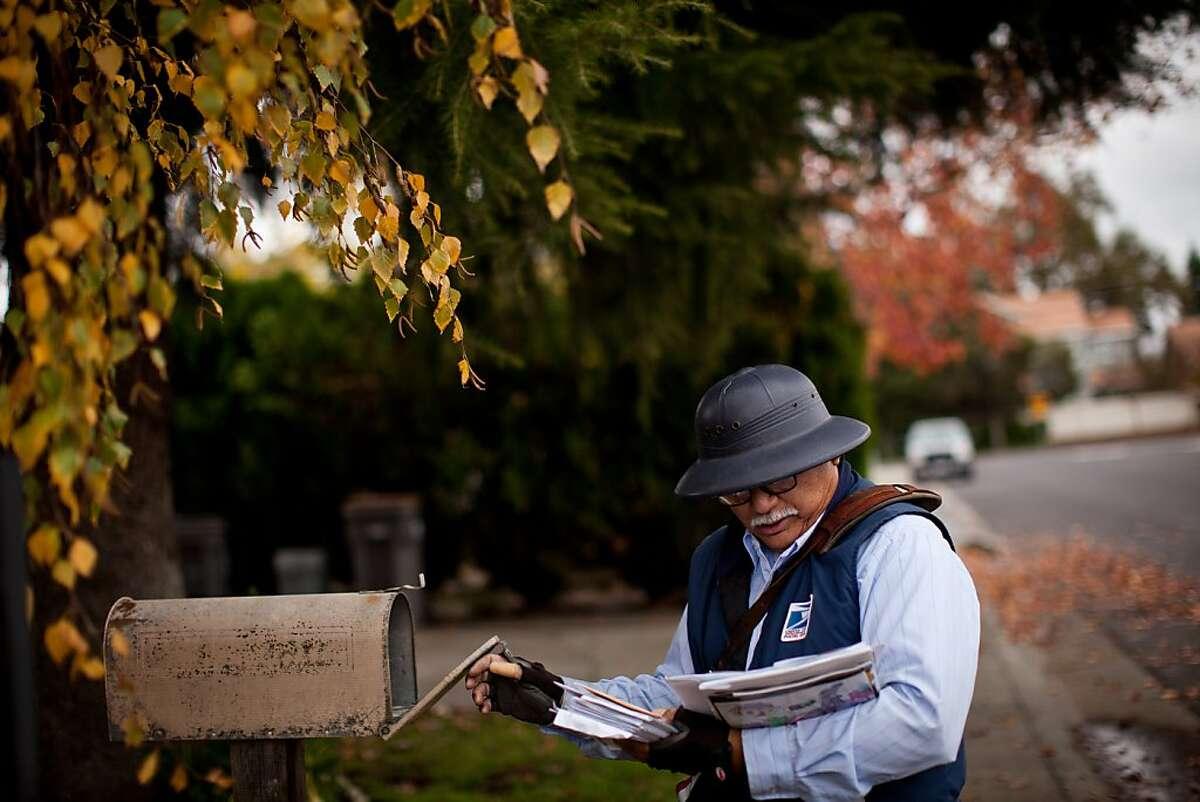 US Postal Service mailman Thomas Laput delivers mail in West Sacramento, Calif., December 6, 2012.