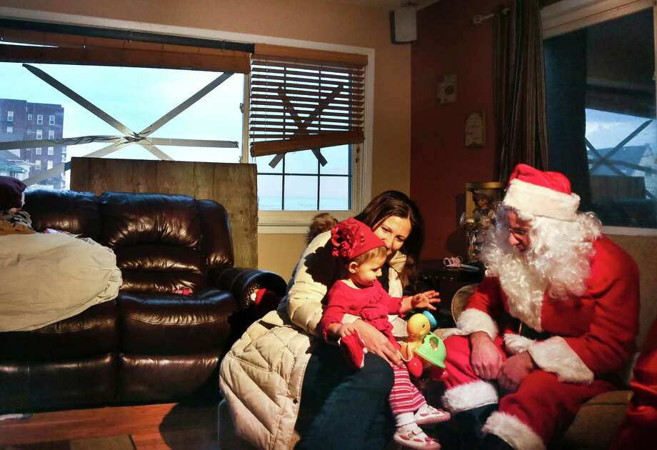 "Elizabeth Sampol holds her daughter, Ella, 14 months, who received a toy from Michael Sciaraffo as ""Santa"", in the Belle Harbor section of the Queens borough of New York. Using Facebook, Sciaraffo started a charitable enterprise to collect and personally deliver toys to children affected by superstorm Sandy, dressed as Santa Claus. Photo: Bebeto Matthews, Associated Press / AP"