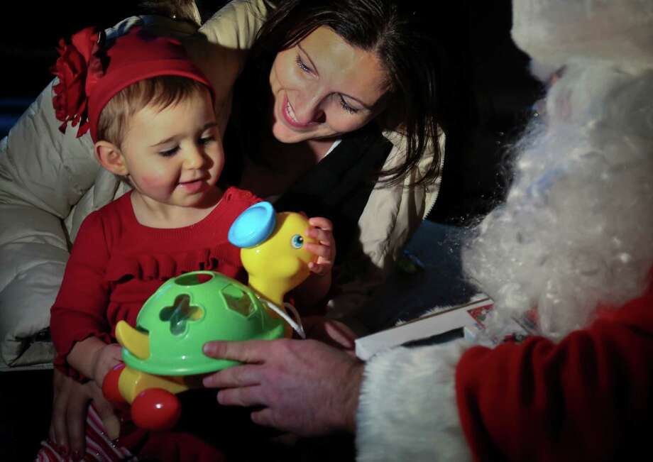 Elizabeth Sampol holds her daughter Ella, 14 months, who received a toy from Michael Sciaraffo, as Santa, in the Belle Harbor neighborhood of the Queens borough of New York. Photo: Bebeto Matthews, Associated Press / AP