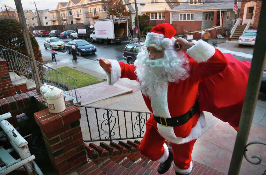 Michael Sciaraffo, as Santa Claus, arrives at the home of the Creamer family to deliver toys in the Belle Harbor neighborhood of the Queens borough of New York. Photo: Bebeto Matthews, Associated Press / AP