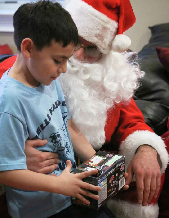 Alex Creamer, 9, receives a toy from Michael Sciaraffo, as Santa Claus, in the Belle Harbor neighborhood of the Queens borough of New York. Using Facebook, Photo: Bebeto Matthews, Associated Press / AP