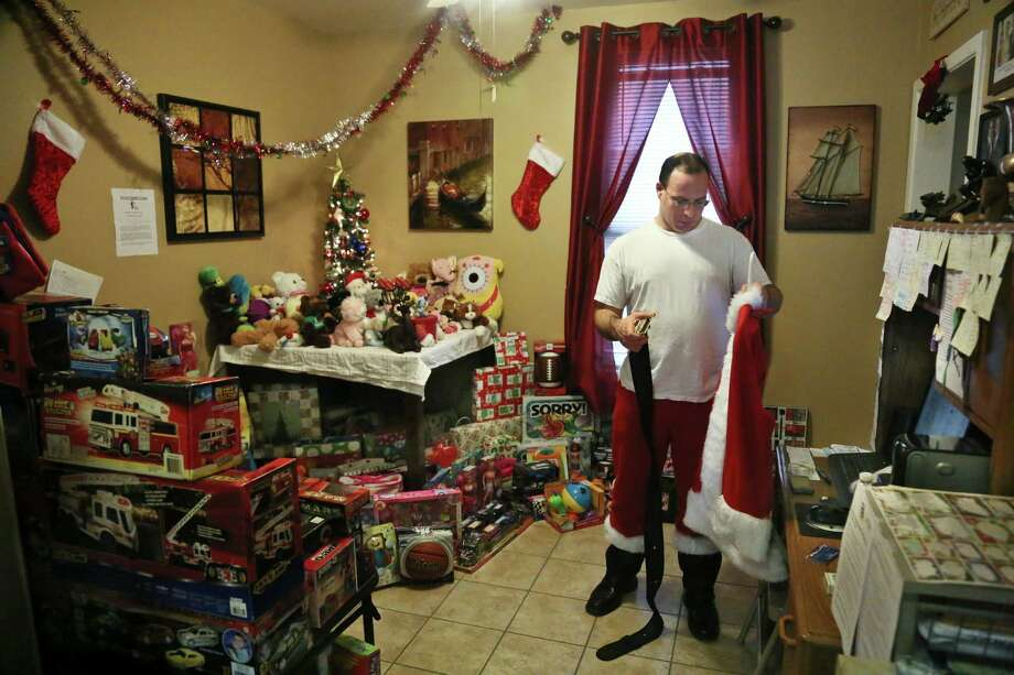 Michael Sciaraffo, a political consultant who has worked for Hillary Clinton and City Hall, is surrounded by donated toys as he prepares his Santa Claus costume, in the Brooklyn borough of New York. Photo: Bebeto Matthews, Associated Press / AP