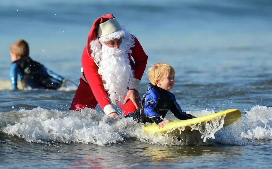 Surfing Santa, Michael Pless, 62, gives a push to a young student, Damen Daugherty, 5, at Seal Beach, south of Los Angeles, on December 21, 2012 in California. Pless, who also runs a surfing school, has been dressing up as Santa Claus and taking to the waves in costume since the 1990's, sometimes joined by his wife Jill in a Mrs. Claus outfit. Photo: FREDERIC J. BROWN, AFP/Getty Images / AFP