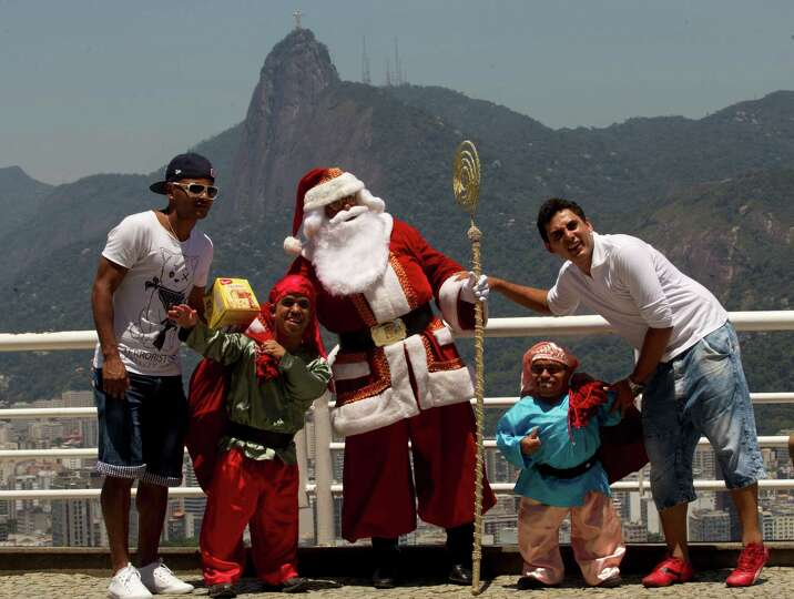 A man dressed as Santa Claus poses for photos with tourists visiting Sugar Loaf mountain in Rio de J