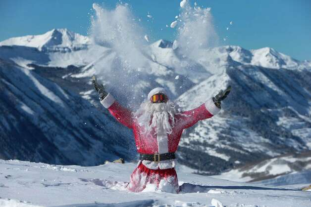 This image provided by Crested Butte Mountain Resort, shows Gregory A. Gull Jr. dressed as Santa throwing fresh snow in the air in Crested Butte, Colo., on Thursday, Dec. 20, 2012. Over 32 inches of snow fell on the mountains during the past seven days. Photo: Nathan Bilow, Associated Press / Crested Butte Mountain Resort